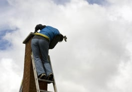 woman on a high extension ladder cleaning a brick chimney